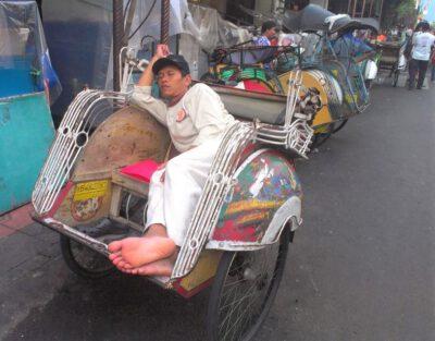 Slapende becakbestuurder, wachtend op zijn ritje door de stad in Jogyakarta